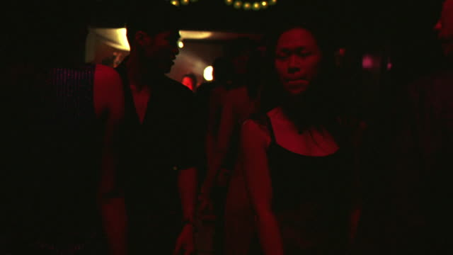 HAND HELD ANGLE OF ASIAN KARAOKE BAR OR NIGHTCLUB. MEN AND WOMEN DANCING, TWO MALE VAMPIRES SEATED ON LOUNGE BITE TWO WOMEN IN THE NECK. VAMPIRE FEEDINGS.