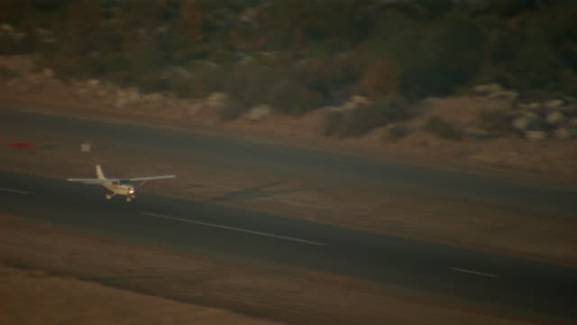 TRACKING SHOT OF WHITE CESSNA 172N IN TAKE-OFF FROM RUNWAY AT AIRFIELD OR AIRPORT. AIRPLANE FLIES FROM LEFT, THEN CIRCLES TO RIGHT AND EXITS LEFT.