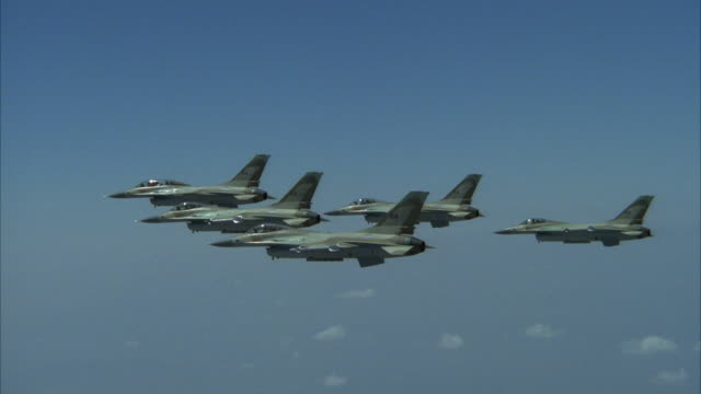 tracking shot of five camouflage f-16 fighter jets flying in a v formation. see formation start to slowly spread apart at end, then reform. see jets fly off screen at left. - jagdflugzeug stock-videos und b-roll-filmmaterial