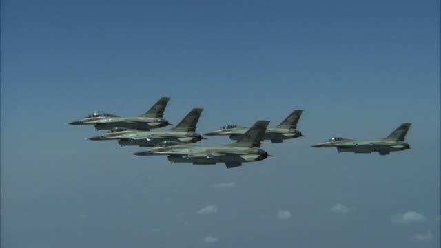vídeos y material grabado en eventos de stock de tracking shot of five camouflage f-16 fighter jets flying in a v formation. see formation start to slowly spread apart at end, then reform. see jets fly off screen at left. - avión de caza