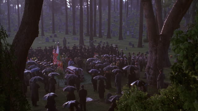stockvideo's en b-roll-footage met zoom in. police funeral. people standing around coffin in cemetery. priest standing next to coffin. zooms in slightly then pulls back. raining heavily. forest. - begrafenis