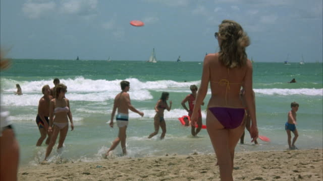 vídeos de stock, filmes e b-roll de medium angle of people on beach. focus on girl in purple bikini bottom and sunglasses walking toward water. pov from behind girl. see tattoo on girl's buttocks. - biquíni