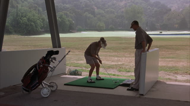 medium angle of woman hitting golf ball at driving range. see mountains, trees, and small pond in background. woman hits, gets frustrated, throws her club, and yells at her male instructor. - driving range stock videos & royalty-free footage