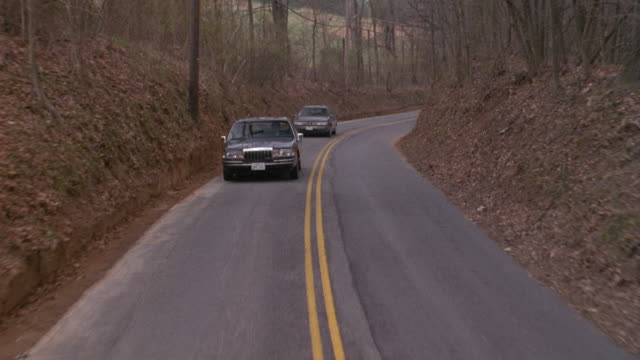 MEDIUM ANGLE MOVING POV OF BLACK LINCOLN TOWNCAR WITH BLACK FORD ESCORT IN BACKGROUND. LEAVES ON GROUND, PROBABLY LATE AUTUMN. COULD BE PART OF MOTORCADE, POSSIBLY GOVERNMENT ESCORT. COUNTRY ROAD.