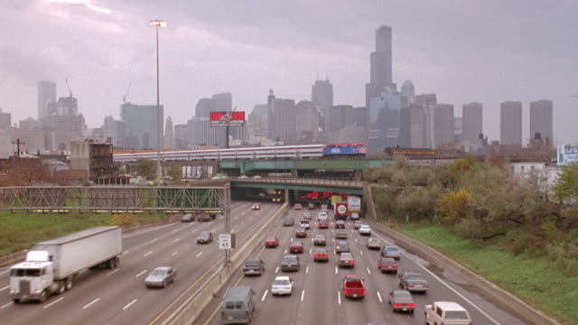 wide angle looking north of chicago skyline with sears tower, highway or freeway, and commuter train over highway moving left to right. traffic on right side of highway, probably morning rush hour. - 1993 stock-videos und b-roll-filmmaterial