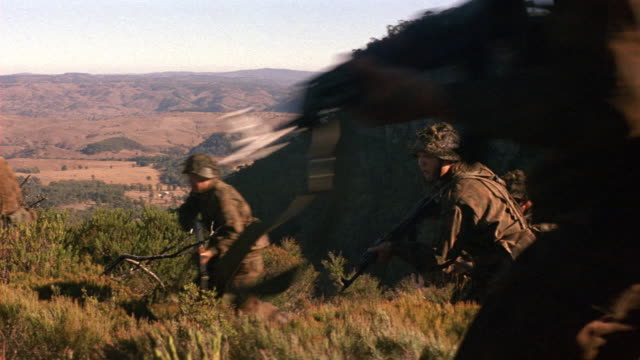 medium angle of dry brush on hillside as north korean soldiers run up hill. soldiers move toward left of screen then pause and hold rifles ready to fire. - north stock videos and b-roll footage