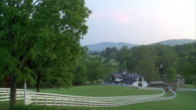 wide angle of horse stable and riding path with white fences on horse farm. see barn on right. forest and hills in background. - pferdestall stock-videos und b-roll-filmmaterial