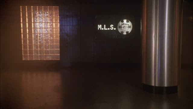 medium angle hallway of sports arena or public building. see sign on wall for m.l.s and image of ball. could be for major league soccer. see flashing lights, could be emergency. - major league soccer stock videos and b-roll footage