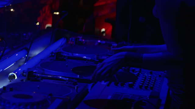 vídeos de stock, filmes e b-roll de medium angle of disc jockeys playing music on turntables in night club. see only hands and arms of disc jockeys playing and scratching records on turntables. see people dancing in background. - 2005