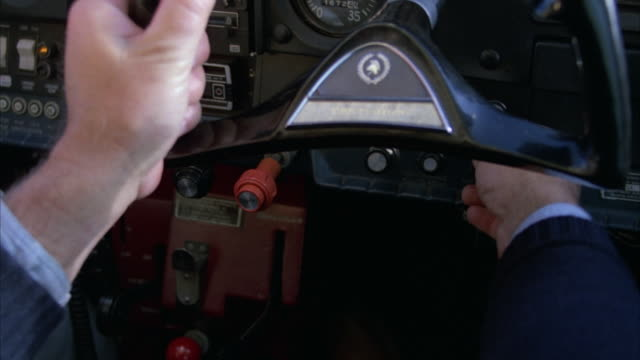 CLOSE ANGLE OF PILOT'S HANDS STEERING AIRPLANE YOKE. SEE NAVY BLUE CUFF OF JACKET AND LEG OF WHITE PANTS AT SIDE. SEE PILOT FRANTICALLY PUSHING AND PULLING BUTTONS ON INSTRUMENT PANEL IN COCKPIT. SEE PILOT LIFT RED LEVER UP BELOW YOKE.