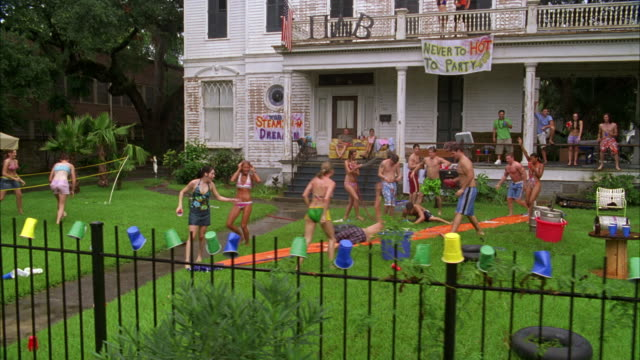 HAND HELD OF COLLEGE STUDENTS  OUTSIDE FRATERNITY OR FRAT HOUSE WEARING BATHING SUITS, DRINKING BEER. A SIGN READS NEVER TO HOT TO PARTY TT05.  DRINKING ON COLLEGE CAMPUS. A LARGE TWO STORY HOUSE OR MANSION. SLIP AND SLIDE.