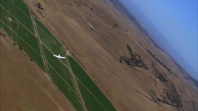 air-to-air aerial tracking shot of small white private jet flying over rural area or farmland. airplanes. planes. corporate jets. - air to air shot stock videos and b-roll footage