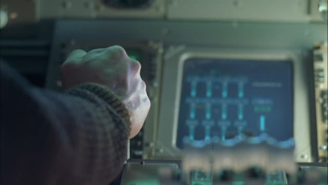 CLOSE ANGLE OF INSTRUMENTS AND CONTROL PANEL IN JET COCKPIT. PILOT HAND PUSHES UP ON SPEED BRAKE LEVER THEN PUSHES UP ON THROTTLE.
