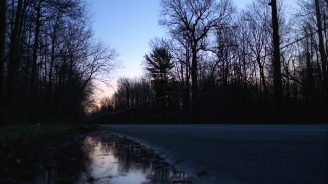 MEDIUM ANGLE OF COUNTRY ROAD WITH FOREST ON BOTH SIDES. TREES HAVE NO LEAVES ON BRANCHES, PROBABLY LATE FALL OR WINTER. BLACK FORD ESCORT DRIVES FROM LEFT TO RIGHT.