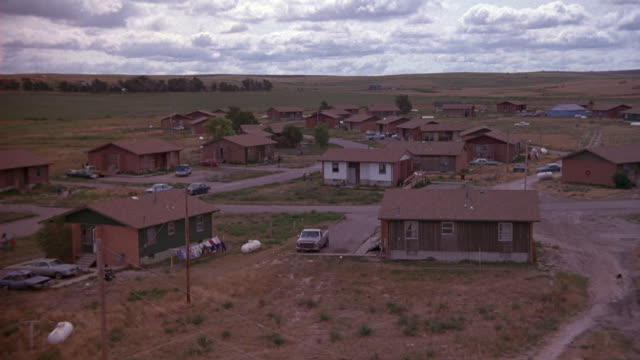 medium angle of one story, lower class houses on indian reservation. police car and two sedans drive from left. - native american reservation stock videos & royalty-free footage