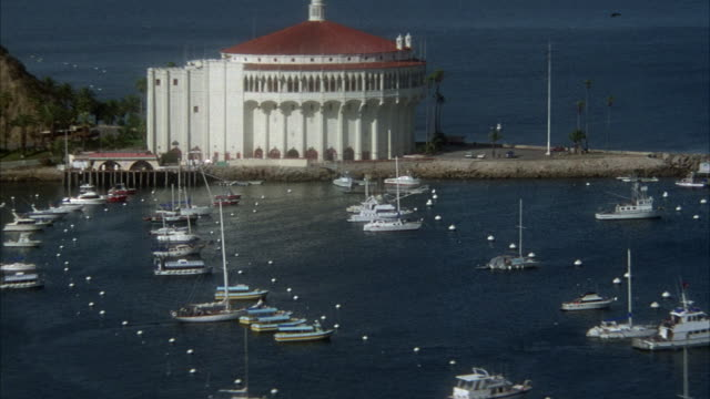 WIDE ANGLE OF SAILBOATS IN HARBOR OF CATALINA ISLAND. SEE CATALINA CASINO IN CENTER BACKGROUND.