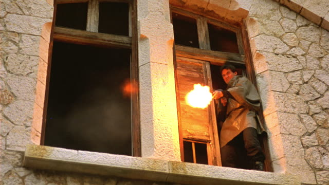 UP ANGLE OF TWO SOLDIERS IN TRENCH COATS STANDING IN  WINDOWS OF STONE BUILDING AND SHOOTING DOWNWARD. MACHINE GUNS. COMBAT. GUNFIRE. MEN. WEAPONS. GUERRILLAS.