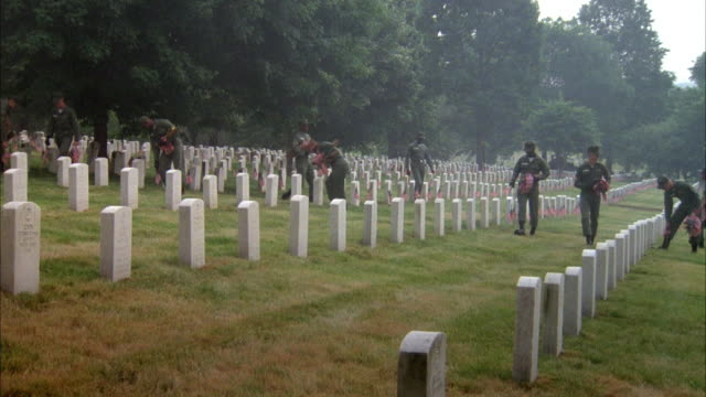 MEDIUM ANGLE OF ARLINGTON NATIONAL CEMETERY. SOLDIERS WALK THROUGH, PLACING AMERICAN FLAGS INTO GROUND IN FRONT OF HEADSTONES, PROBABLY FOR MEMORIAL DAY.