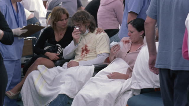 stockvideo's en b-roll-footage met medium angle of nurses, men and women in crowded hospital triage area. patients wear face masks, some people coughing up blood.  clinics, medical centers. could be emergency room. - triage