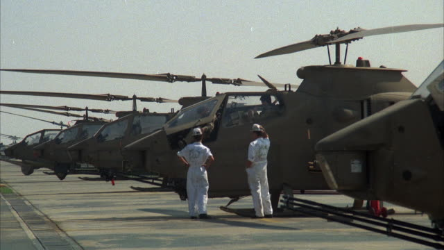 medium angle of cobra military helicopters lined on runway. two mechanics converse in front of helicopter. middle east. attack helicopters. - military helicopter stock videos & royalty-free footage