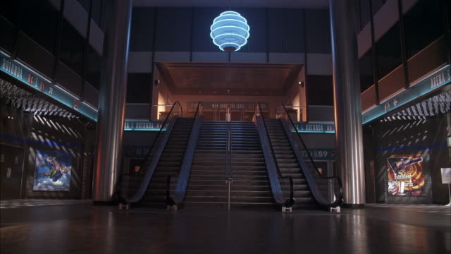 vídeos de stock e filmes b-roll de up angle steps and escalators from empty lobby area of madison square garden. see blue neon art deco chandelier hanging from ceiling. orange colored lights flashing on upper level wall. - madison square garden