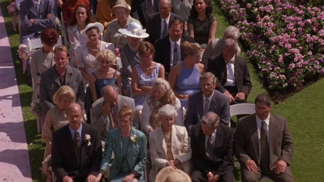 HIGH ANGLE DOWN OF AUDIENCE, WEDDING GUESTS SITTING IN WHITE CHAIRS AT AN OUTDOOR WEDDING. PEOPLE, WOMEN, MEN, COUPLES TALKING TO EACH OTHER. PINK FLOWERS AND GREEN GRASS FRAME RIGHT.