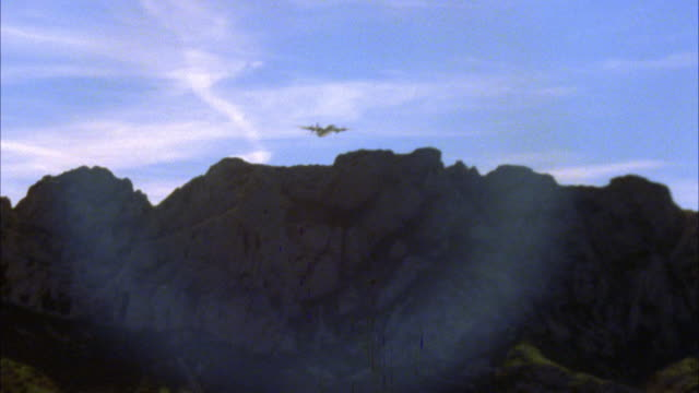 UP ANGLE OF MILITARY BOMBER AIRPLANE FLYING OVER MOUNTAINS.