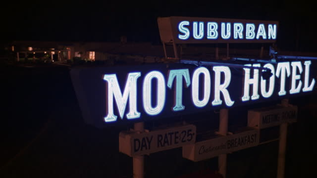 CLOSE ANGLE OF BLUE NEON SIGN. SEE SUBURBAN MOTOR HOTEL TEXT IN NEON BLUE. SEE T OF MOTOR FLICKER DIMLY. SEE IN BLACK TEXT SIGNS BELOW NEON SIGN DAY RATE $25, MEETING ROOM, AND CONTINENTAL BREAKFAST.