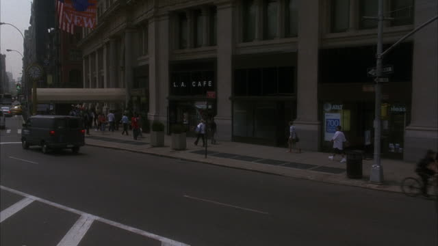 wide angle on pedestrians walking past storefronts beside new york city street. see a restaurant reading l.a. cafe. camera pans from r-l to the flatiron building. fifth avenue. madison square. - flatiron building manhattan stock videos and b-roll footage