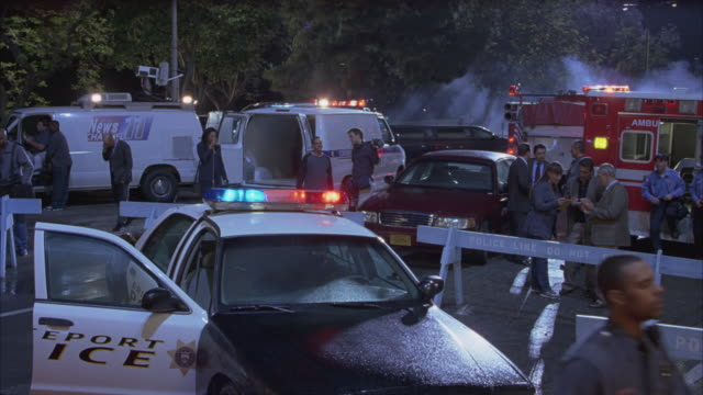 pan right to left of police around bridgeport police cars, fire trucks, ambulances and news vans with reporters in parking lot of emergency.  possibly crime scene. - 犯行現場点の映像素材/bロール