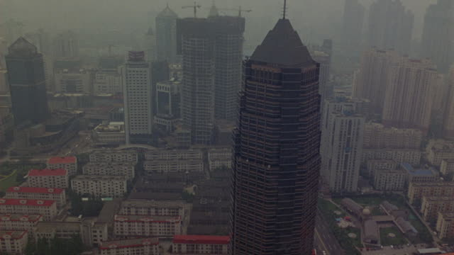 aerial view of downtown shanghai skyline. skyscrapers or multi-story or high rise building in background. could be office buildings or apartments or hotels. cars driving on streets below. - office block exterior stock-videos und b-roll-filmmaterial