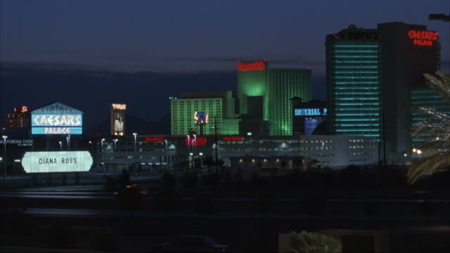 medium angle of caesar's palace hotel and casino. pans left to neon cube sign that reads blvd, then down to people in evening wear, limo, and red carpet, possibly outside club. - red carpet event stock videos & royalty-free footage