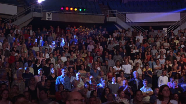 wide angle of concert crowd.  see people start to dance and cheer.  see disco lights move over audience. - anno 2001 video stock e b–roll