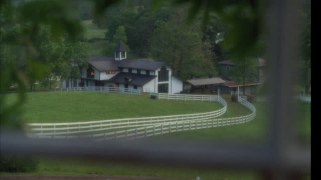 medium angle pov through window. see farm, probably horse farm, with large building and barn. large building could be another barn or stables. twin white fences for horse riding path winds way across frame. - pferdestall stock-videos und b-roll-filmmaterial
