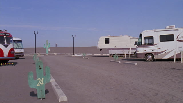 wide angle of desert parking lot. could be for campground or national park. rvs, campers parked. could be trailer park. sign markers shaped like cactuses. - cactus stock videos & royalty-free footage