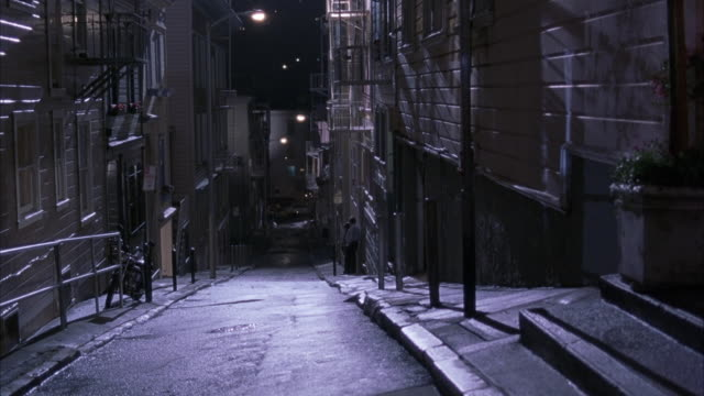 wide angle of alley between apartment buildings in san francisco at night. moon reflection on streets. see two people walking away from camera at bottom of hill. - gasse stock-videos und b-roll-filmmaterial