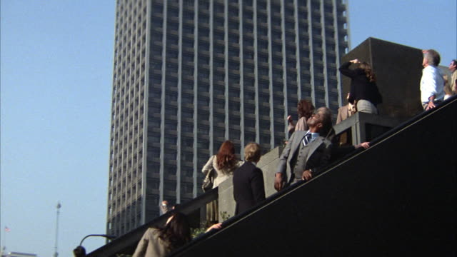 medium angle of pedestrian plaza with crowd traveling up and down escalators on right. people look up to sky with confusion. downtown office buildings in background. - anno 1983 video stock e b–roll