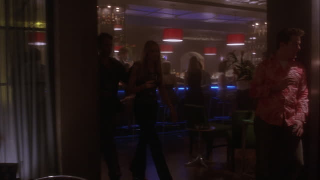 vídeos de stock, filmes e b-roll de medium angle. camera follows a couple of women entering nightclub, bar. camera pans around nightclub on people drinking and conversing with each other. also see several couples dancing. - bar