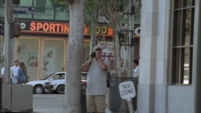 vídeos de stock e filmes b-roll de medium angle moving pov of city street or hollywood blvd and hollywood walk of fame. see storefronts and pedestrians. see man with video camera filming. - bulevar