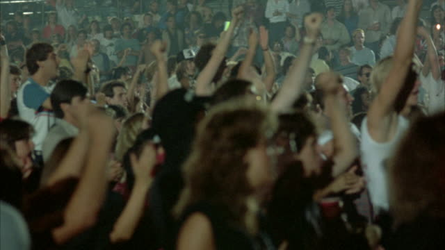 CLOSE UP PAN L-R ACROSS ROCK CONCERT AUDIENCE (YOUNG AND DRESSED IN EARLY 1980'S ATTIRE). CROWD RISES UP FROM THEIR SEATS WITH ARMS RAISED, CLAPPING AND PUMPING THE AIR, AS SHOT SLOWLY PANS ACROSS THEM