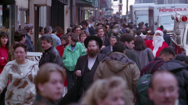 wide angle of crowds of people walking down sidewalk. see man in santa claus costume at right waving to people and trying to solicit donations. see storefronts at left and delivery trucks at right. christmas. - 1995 stock-videos und b-roll-filmmaterial