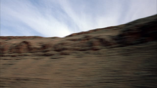 AERIAL UP ANGLE OF ROUNDED CLIFFS OF HILLS. JET TRAVELS TO LEFT.  SEE ROCKY BROWN HILLTOPS. BLUE SKY STREAKED WITH WHITE WISPY CLOUDS.