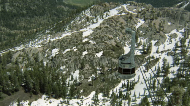 tracking shot, down angle of a gondola or aerial cable car approaching ski lodge or ski resort on top of mountain. snowy mountain, forest visible below. cable wires. - ski lodge stock videos & royalty-free footage