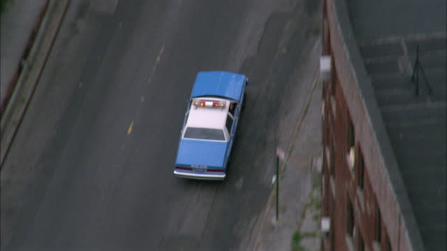 vídeos de stock, filmes e b-roll de aerial tracking shot of nypd police car driving on city street past other cars. see bizbar flashing. - 1980 1989