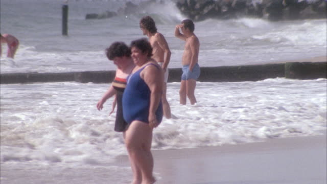 medium angle of two women wading into water. see one woman wearing a black bathing suit with skirt bottom. see other woman in a one piece blue bathing suit. see a man in white swimming trunks with daughter and other people in background. - swimming trunks stock videos & royalty-free footage