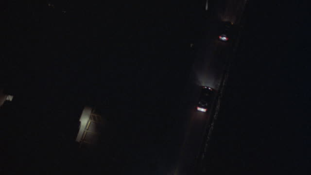 aerial tracking shot of motorcade of cars driving along highway or country road. could be police, detective, or federal agency. cars turn and continue driving down street or highway. rural area. - police car stock videos and b-roll footage
