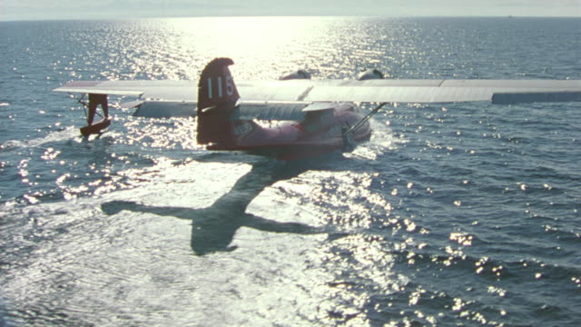 aerial of red seaplane or water plane after landing in water. camera circles around plane as it moves slows down in water. sun reflecting ocean surface. twin propeller, airplane, aircraft, horizon. - 水上飛行機点の映像素材/bロール