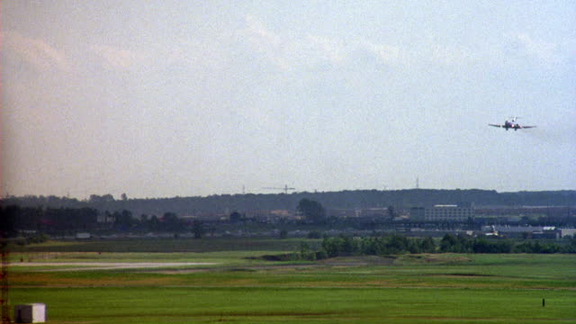 tracking shot of commercial airliner, airplane, plane landing on runway at airport from right. pov is from airport terminal. - luftfahrzeug stock-videos und b-roll-filmmaterial