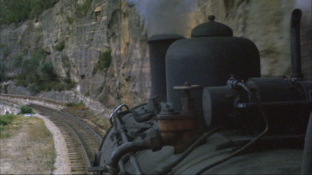 medium angle of pov mounted on black steam engine train. see train moving along tracks. see steam billowing out from vent on top. see gray rock wall on right. - locomotive stock videos & royalty-free footage