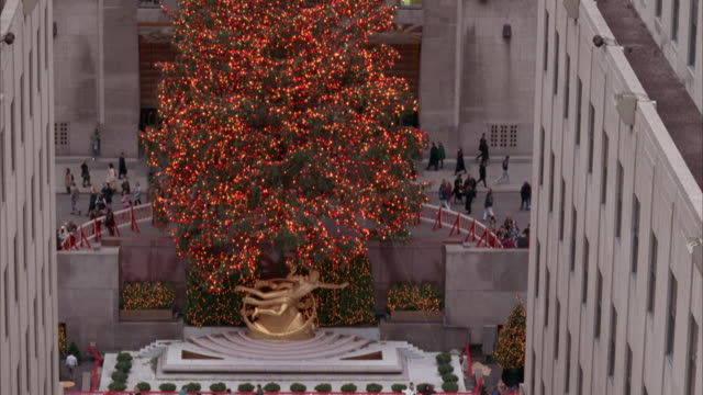 vídeos y material grabado en eventos de stock de medium angle pan down and up of giant christmas tree at rockefeller center. see gold statue and ice skating rink at base of christmas tree. people skate as crowd is in front of rink. pans up, see christmas tree and office building in background. - centro rockefeller
